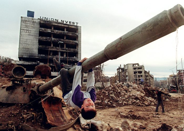 In this photo taken on April 22, 1996 a young boy plays on a tank in the Sarajevo neighbourhood of Grbavica.