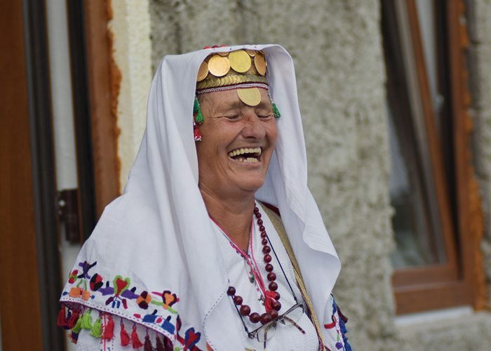 A local Lukomir woman laughing in traditional bosnian village highlands costume clothing