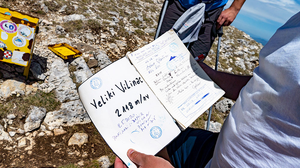 Writing our names into a mountain books of Veliki Vilinac peak at Cvrsnica mountain